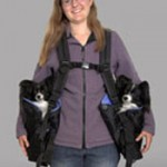 Young woman carrying two small dogs, one in each side bag of her BackTpack