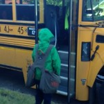 Young boy getting onto a school bus with BackTpack