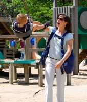 Mom using her BackTpack with her kids on the playground