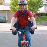 Boy happily riding his bike to school with comfort and balance wearing his BackTpack