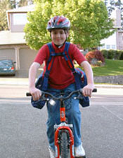 young boy riding a bike with BackTpack