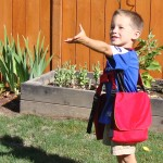 3 year old boy wearing red BackTpack Mini doesn't notice he is carrying some books while he is playing naturally