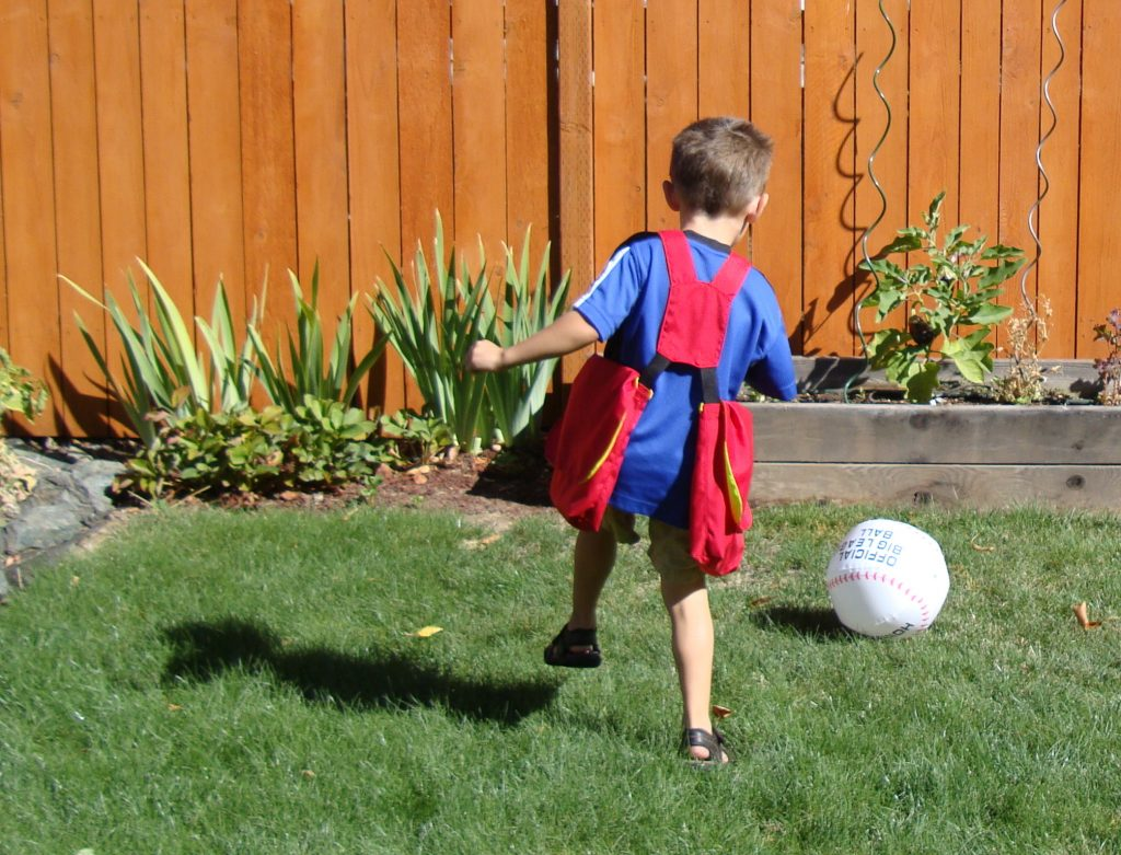 Back view of young boy wearing red Mini playing kickball