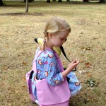 Young girl wearing pink BackTpack Mini squatting down to find seeds on the ground
