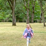 Young girl wearing pink BackTpack Mini running joyfully in the park