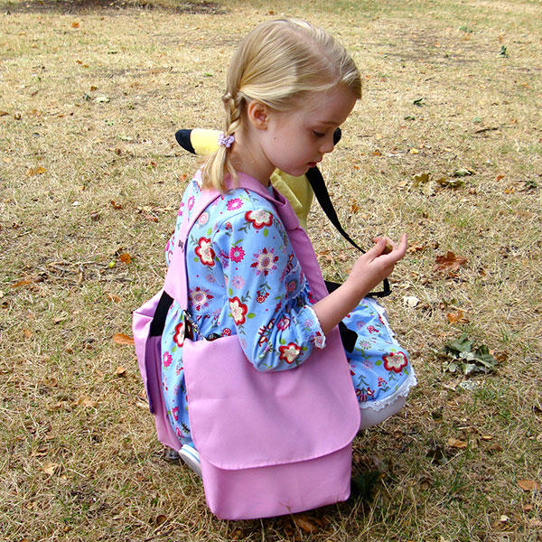 Girl croutched to the ground looking for seeds while wearing her BackTpack Mini