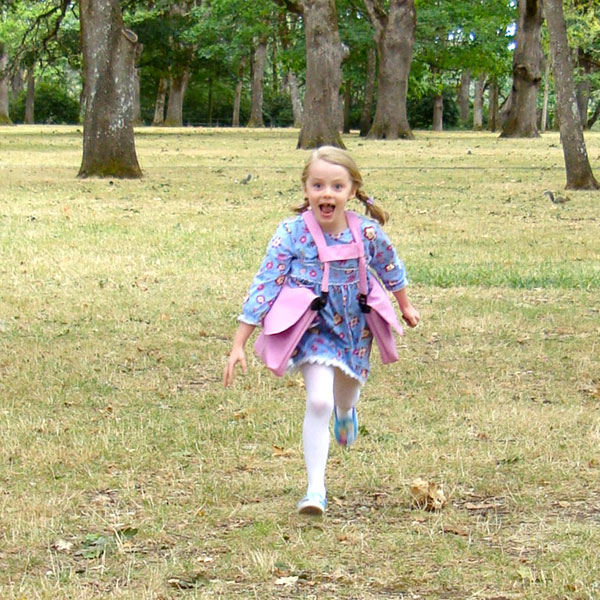Little girl running wearing a pink BackTpack Mini