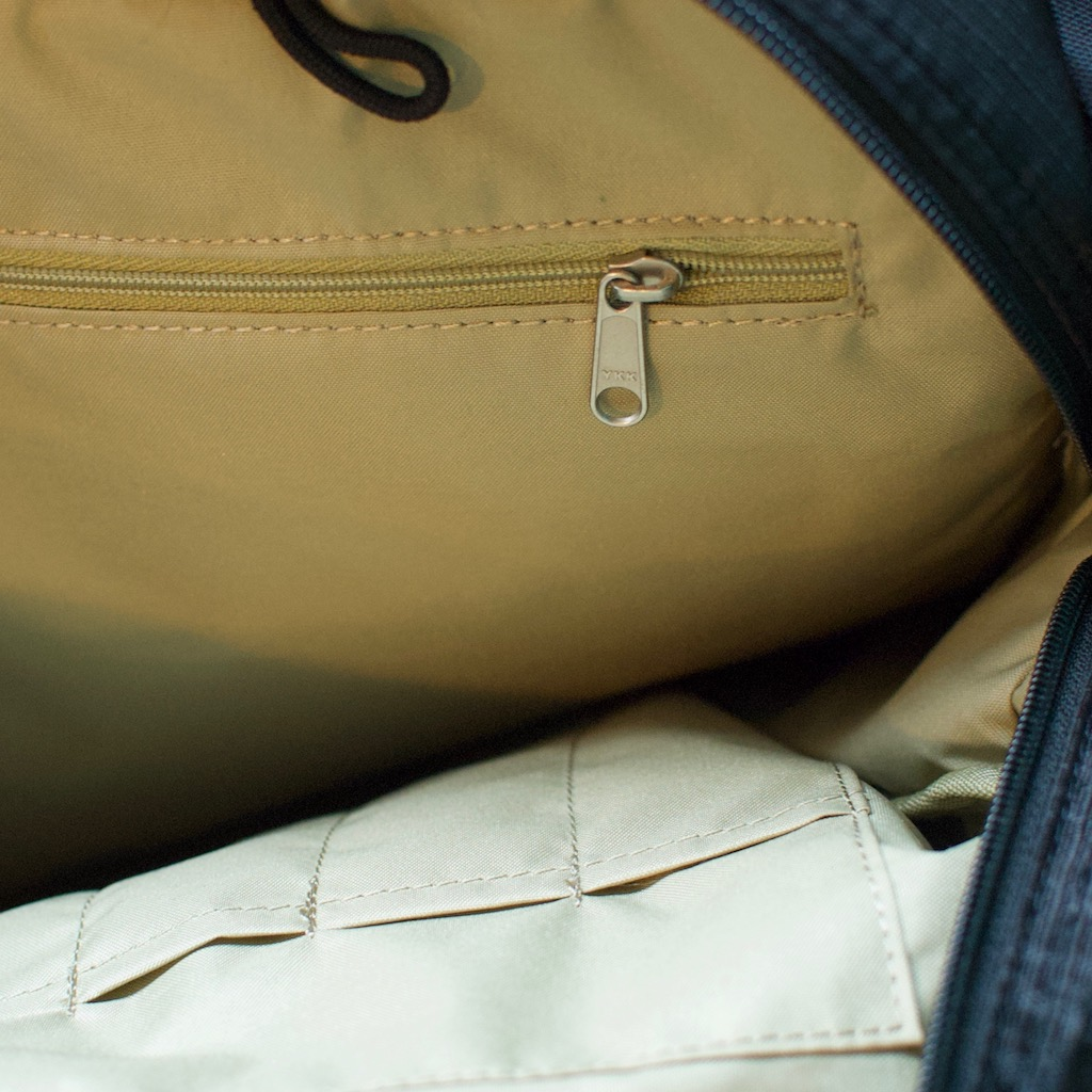 Detail photo of BackTpack 3.1 khaki interior of black bag, showing key fob, interior zipper, pen pockets, and loop for hydration pack