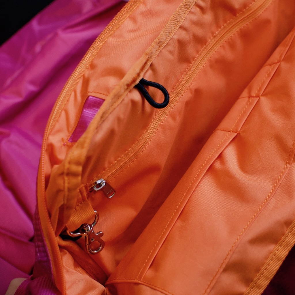 Detail photo of BackTpack 3.1 orange interior of magenta bag, showing key fob, interior zipper, pen pockets, and loop for hydration pack