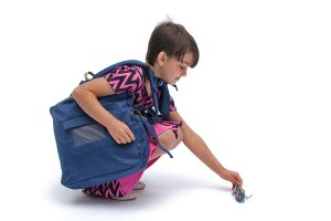 Showing balance and ease of stooping to pick something up wearing BackTpack with its Lap-Strap feature