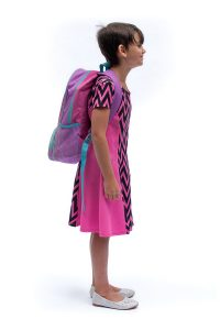 Girl demonstrating forward-lean posture common when wearing a standard backpack