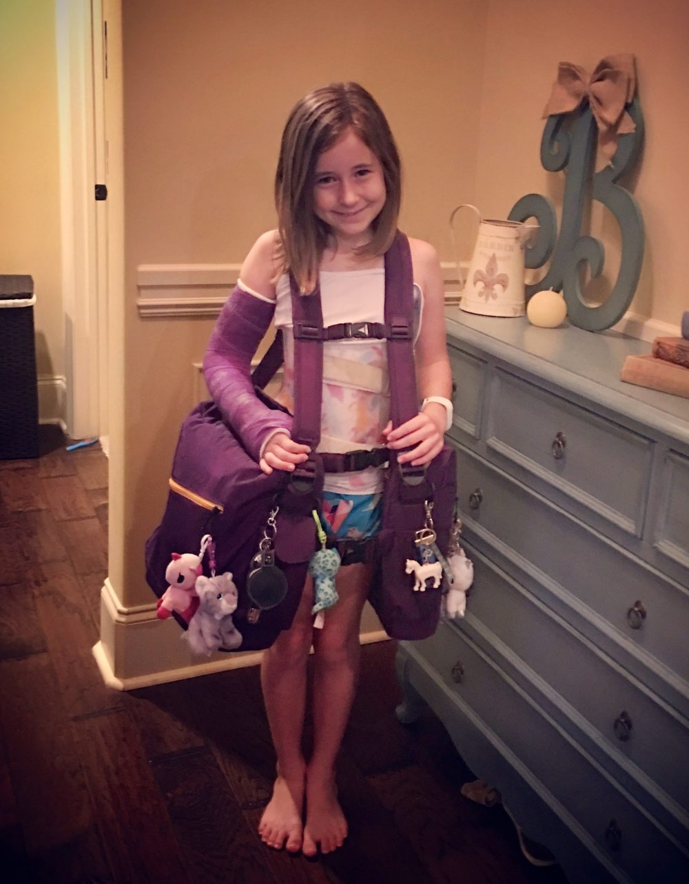 Little girl with scoliosis brace and her purple BackTpack for school