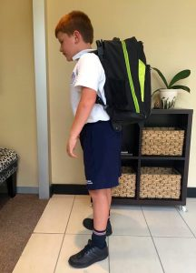 Young boy bent over with a heavy backpack